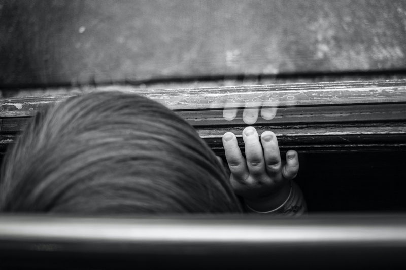 Black and white photo of the top of a child's head with their hand resting on a window.